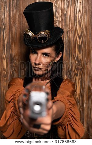 Selective Focus Of Serious Steampunk Woman In Top Hat With Goggles Aiming With Pistol At Camera On W