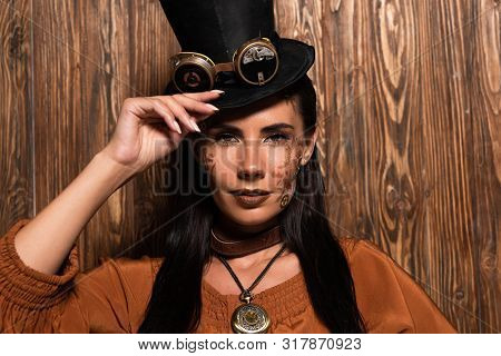 Front View Of Steampunk Woman Touching Top Hat With Goggles Looking At Camera On Wooden