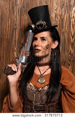Pensive Steampunk Woman In Top Hat With Goggles Holding Pistol On Wooden