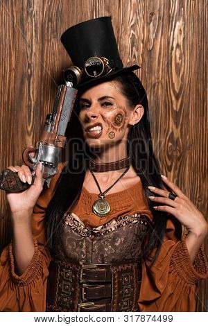 Irritated Steampunk Woman In Top Hat With Goggles Holding Pistol On Wooden