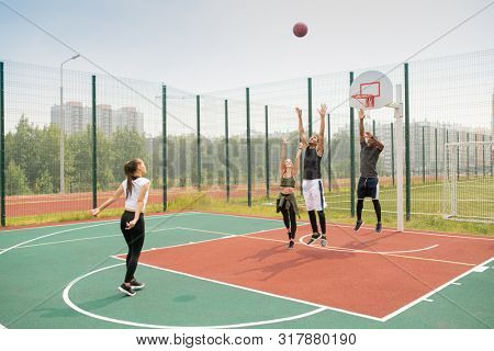 Team of young intercultural friends or students working out on basketball court