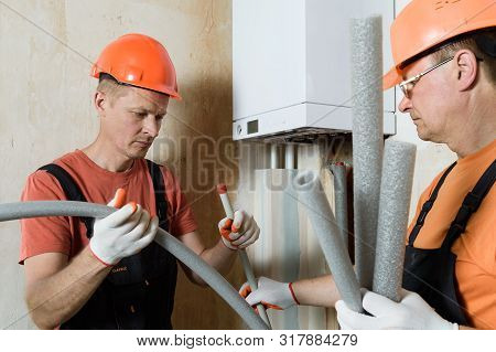 Workers Are Installing Thermal Insulation On The Pipes Of A Home Gas Boiler.
