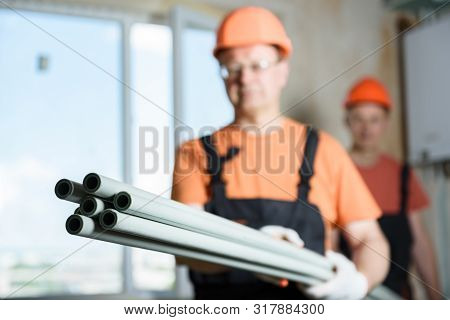 Plastic Pipes For Plumbing And Home Heating In The Hands Of Workers.