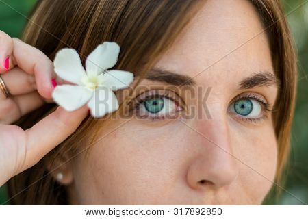 Close Up Portrait Of A Young Woman With Blue Eyes With Green Plants On The Background