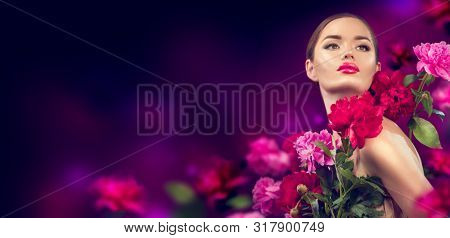 Beautiful Girl With purple, red, pink Peony Flowers portrait. Beauty high fashion Model Woman Face with peony flower close-up . Perfect Skin. Professional Make-up. Makeup. Vogue style Fashion Art