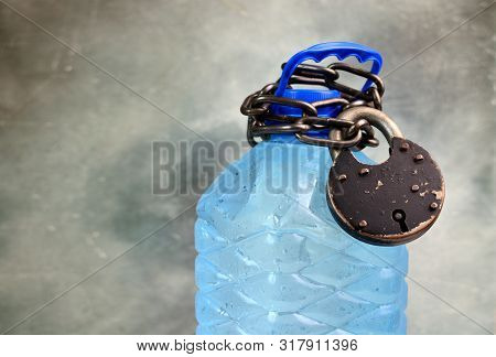 Drought And Water Scarcity Concept With Plastic Bottle With Fresh Water, Chain And Lock. Great Value