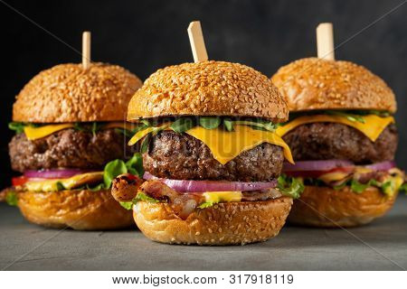 A Set Of Homemade Delicious Burgers Of Beef, Bacon, Cheese, Lettuce And Tomatoes On A Dark Concrete