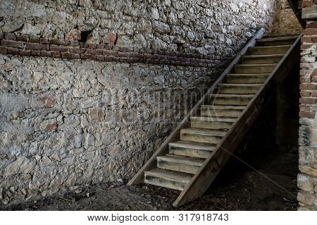 Old Wooden Stairs To The Attic In An Old House. Old Wooden Stairs In A House Built Of Stone Walls
