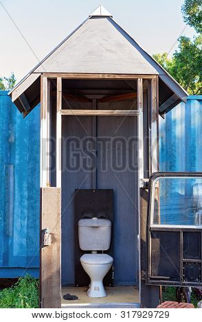 A Crudely Built And Comical Timber Outdoor Toilet Enclosed By A Car Door And Window