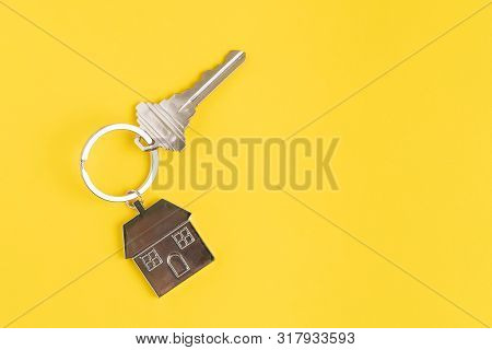 Home Key With House Keyring Or Keychain On Solid Yellow Background Using As Home Ownership, Mortgage