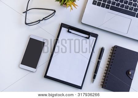 Empty Screen Smart Phone And Tablet With Laptop On Business Desk Office With Copy Space, Top View