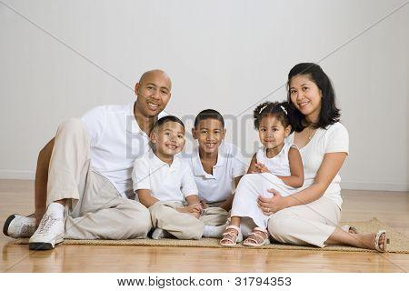 Portrait of multi-ethnic family on floor