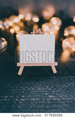 Blank Artist Canvas Surrounded By Lightbulb String Lighs