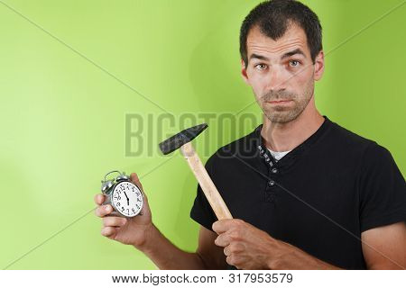 Portrait Of Shocked Man Holding Round Clock Isolated And Hummer On Yellow Wall Background In Studio.