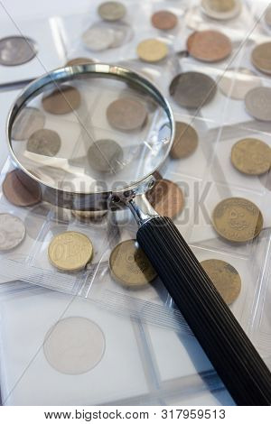 Different old collector's coins with a magnifying glass, soft focus background poster