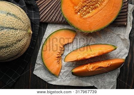 Flat Lay Composition With Ripe Cantaloupe Melon On Black Wooden Table