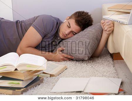 Universität Schüler junge schlafend auf dem Boden des Wohnzimmers, umgeben von Büchern und Noten, erschöpft von st