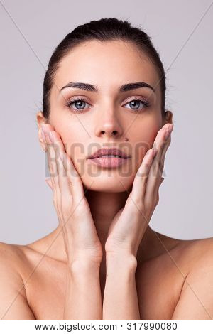 Portrait Of Beautiful Brunette Woman With Hands Near Her Face And Clean Fresh Skin Isolated On Light