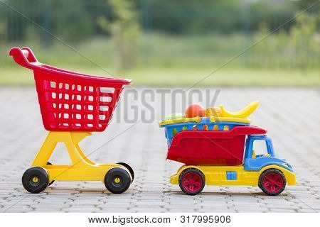 Bright Plastic Colorful Toys For Children Outdoors On Sunny Summer Day. Car Truck Carrying Basket Wi