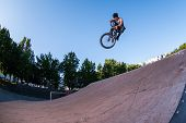 Bmx stunt performed at the top of a jump ramp on a skatepark. ramp on a skatepark. poster