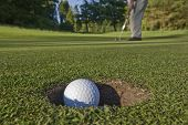 A golfer sinks a long putt and watches the ball dive into the hole. poster
