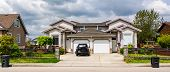 Residential duplex townhouse with black car parked on concret driveway poster