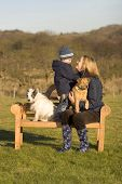a mother and her young son sitting on a park bench while out walking the dogs t-shirt