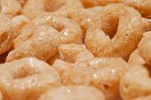 Closeup of sugary coated cereal o's showing texture of wheat and shine from sugar poster