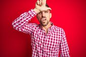 Young handsome man over red isolated background making fun of people with fingers on forehead doing loser gesture mocking and insulting. poster