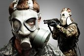 young soldiers wearing gas mask over grey background poster