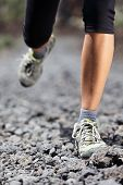 Trail runner woman running on mountain path with rocks. Running shoes and legs closeup of female fitness sport model during outdoor workout. poster