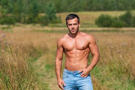 Caucasian Shirtless Man Brunet With A Tanned Shirtless Body In Jeans Stands On A Country Road