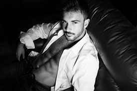Handsome Man With Beard And Open Shirt Revealing Muscular Abs Sitting In Leather Armchair Looking At