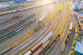 Aerial View Flight Over Rail Sorting Freight Station With Various Wagons, With Many Rail Tracks Rail