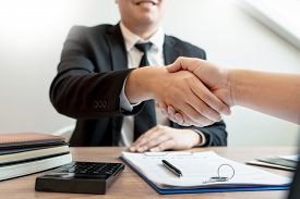 Customer And Broker Shake Hands Agreeing To Buy New House At Meeting After Making Sale Purchase Deal