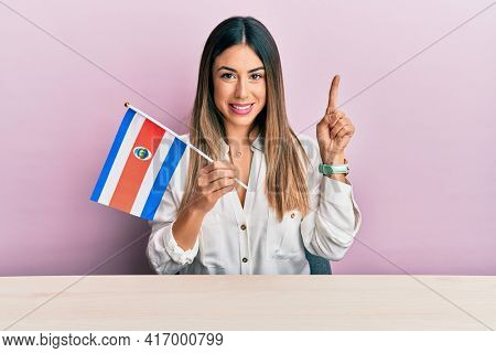 Young hispanic woman holding costa rica flag sitting on the table smiling with an idea or question pointing finger with happy face, number one