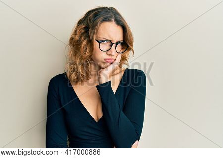 Young caucasian woman wearing business shirt and glasses thinking looking tired and bored with depression problems with crossed arms.
