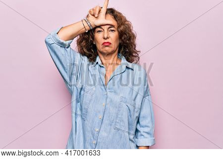 Middle age beautiful woman wearing casual denim shirt standing over pink background making fun of people with fingers on forehead doing loser gesture mocking and insulting.