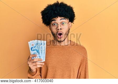 Young african american man with afro hair holding 50 thai baht banknotes scared and amazed with open mouth for surprise, disbelief face