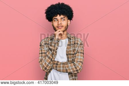 Young african american man with afro hair wearing casual clothes with hand on chin thinking about question, pensive expression. smiling with thoughtful face. doubt concept.