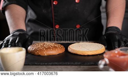 Step By Step Recipe. Stage 1. The Chef Prepares A Delicious Burger. Close-up Of Hands In Black Glove