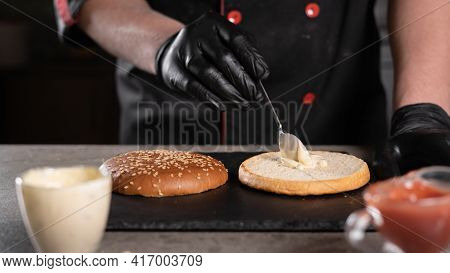 Step By Step Recipe. Stage 2. The Chef Prepares A Delicious Burger. Close-up Of Hands In Black Glove