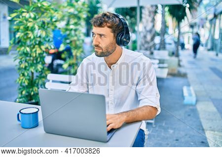 Handsome man with beard wearing casual white shirt on a sunny day working using laptop and wearing headphones at cafeteria