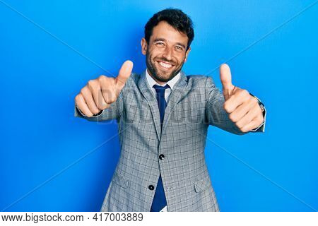 Handsome man with beard wearing business suit and tie approving doing positive gesture with hand, thumbs up smiling and happy for success. winner gesture.