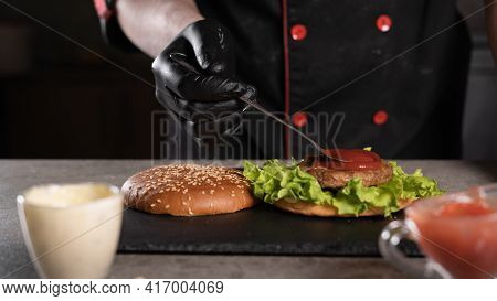 Step By Step Recipe. Stage 5. The Chef Prepares A Delicious Burger. Close-up Of Hands In Black Glove