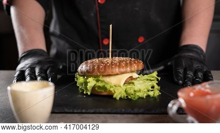 Step By Step Recipe. Stage 9. The Chef Prepares A Delicious Burger. Close-up Of Hands In Black Glove