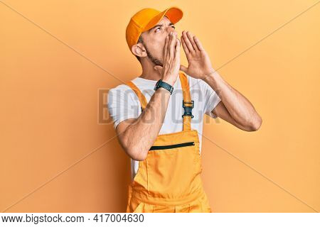Hispanic young man wearing handyman uniform shouting angry out loud with hands over mouth