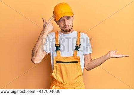 Hispanic young man wearing handyman uniform confused and annoyed with open palm showing copy space and pointing finger to forehead. think about it.