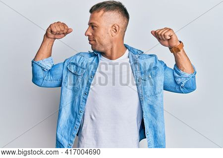 Handsome muscle man wearing casual denim jacket showing arms muscles smiling proud. fitness concept.