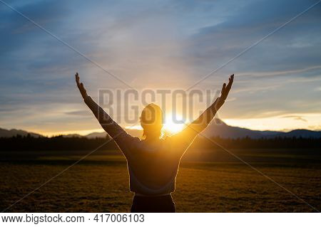 View From Behind Of A Woman Embracing Life Standing Outside In A Beautiful Meadow With Her Arms Rais